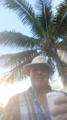 The writer and his coffee under a palm tree
